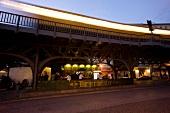 People dining at Burgermeister under bridge at night