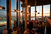 People at restaurant looking at night view through panoramic window, Hamburg, Germany