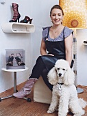 Portrait of woman sitting on chair with dog sitting on ground besides her, smiling