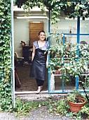 Shoemaker Anja Hoffmann standing at door, smiling