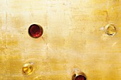 Glasses of white wine and red wine on a golden surface (seen from above)
