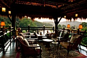 People relaxing on terrace of Chiang Saen Luxury Hotel overlooking river, Thailand
