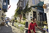 People walking on alley beside restaurant in Cesme, Turkey, blurred motion