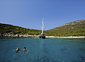 People swimming in sea in front of sailboat in Bodrum, Mugla Province, Turkey