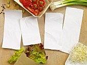 Four blank pieces of paper surrounded by salad ingredients