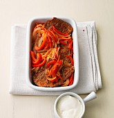 Beef steaks with an onion and pepper medley in a baking dish