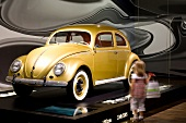 Child looking at VW Beetle in the gazebo, Autostadt Wolfsburg, Germany, blurred motion