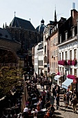 People at cafe and walking on street, Cathedral church on background, Aachen, Germany