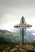 View of Summit cross with mountain range and clouds in Allgaeu, Germany