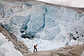 Hiker in front of ice wall in Aletsch Glacier, Marjelesee, Valais, Switzerland