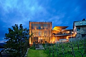 View of illuminated wine factory in cube shape with winery in front, Wurzburg, Germany