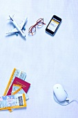 Aircraft model, mobile, glasses, computer mouse and travel documents on white background