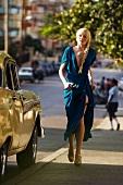 Frau blond, Zopf, Abendkleid blau, in Eile, Blick seitlich