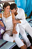 Loving couple in white outfit, man kissing woman's shoulder, smiling