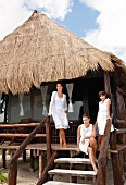 Mother with daughters in white outfit standing and sitting on terrace of beach house