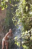 Junge Frau in Slip und Bikini duscht im Freien vor einer Felswand