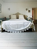 Antique double bed with white bedspread in Tuscan country house