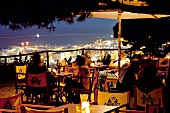 Guests sitting on terrace of La Caseta Club at night in Barcelona, Spain