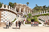 Tourists sitting at entrance of Park Guell, Barcelona, Spain