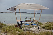 Laid table attached with sun umbrella on beach