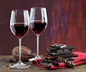 An arrangement of red wine glasses, cocoa beans and a stack of chocolate
