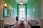View of green wall and bathroom with bathtub at Castle Gaussig, Saxony, Germany