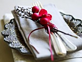 A place setting decorated for Christmas with a napkin, a twig and baubles