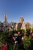 View of cityscape overlooking people sitting on rooftop bar at New York, USA