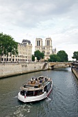 View of Notre-Dame and boat in Seine river, Paris, France