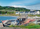 View of fishing boat at coast, mountains and building in Rathlin Island, Ireland