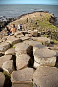 Tourists relaxing on Giant's Causeway at Antrim coast, Ireland