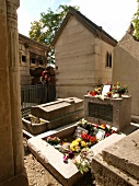 Grave with flowers and candles in Pere Lachaise Cemetery, Paris, France