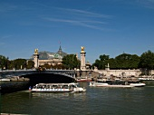 Ferry passing below of Pont Alexandre III over Seine river in Paris, France