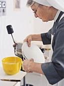 Hostienbäckerin Schwester Revokata begradigt Hostienkuchen