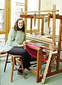 Portrait of weaver Antigone Hochstedt sitting at her loom, Frellstedt, Germany