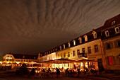 Schwetzingen: Schlossplatz, abends, Tische, beleuchtet.