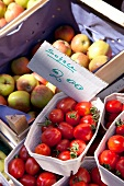 Fresh tomatoes and apples with price label in boxes