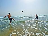 Boys playing football in water at Patara beach, Turkey