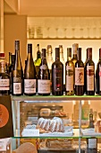 Wine bottles and cake on counter at wine bar in Vienna, Austria