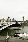Ferries passing under Alexander III bridge in Paris, France