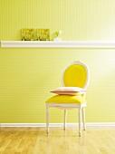 Wand mit grüner Tapete und Stuckleiste als Ablagefläche, davor Stuhl mit Kissen
