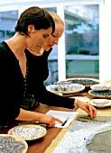Mosaic artist Nicole Zach with an employee at work