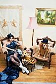Frau sitzt im Abendkleid im Sessel, daneben Hund im Sessel