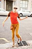 Frau in Wildlederhose und rotem Shirt, bleibt mit Absatz hängen