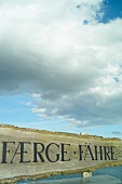 Wooden sign board with cloudy sky in background, Baltic Sea Coast