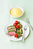 Lamb with a herb crust, courgette and tomatoes