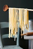 Fresh tagliatelle hanging from a wooden spoon to dry