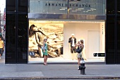 Woman photographing other woman in front of Advertisement on 5th Avenue, New York