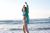 Frau im Bikini und transparenter Bluse am Strand, hebt die Arme