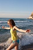 Frau läuft am Strand durchs Wasser Arme ausgebreitet